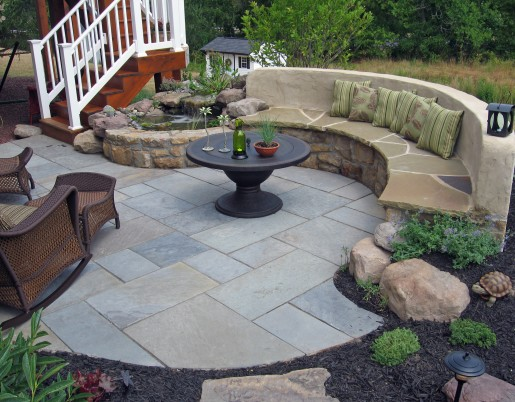 Flagstone patio, small waterfeature, stone and stucco seat bench and landscaping