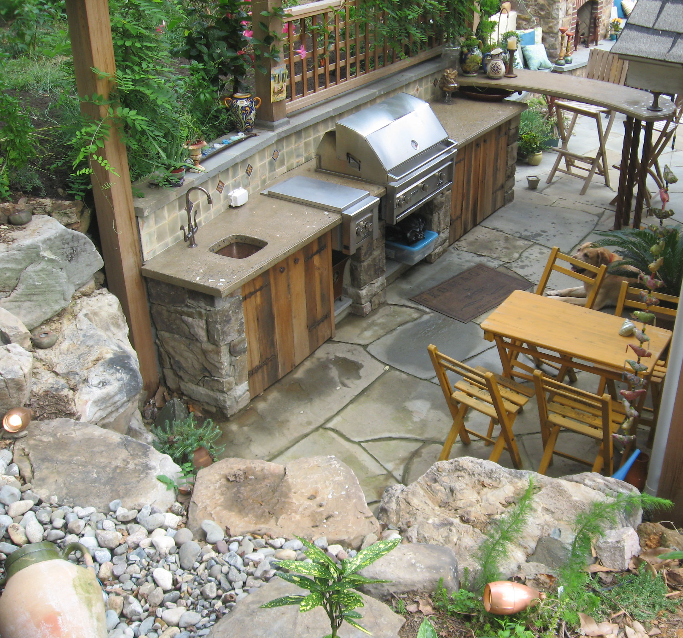 Outdoor kitchen featuring a concrete countertop, custom cabinets, wash sink and built-in barbeque.-Baltimore MD