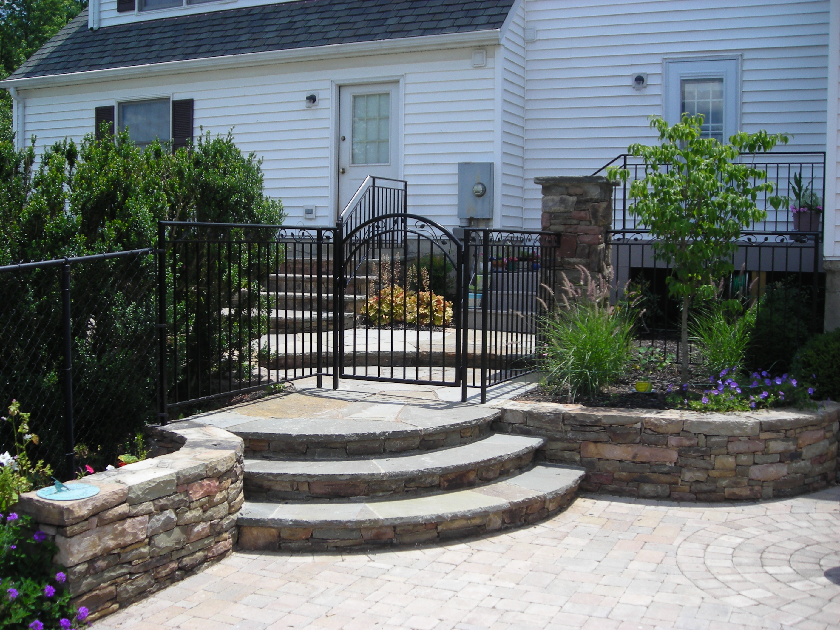 Custom Stone Walls adjoining to stone steps and patio
