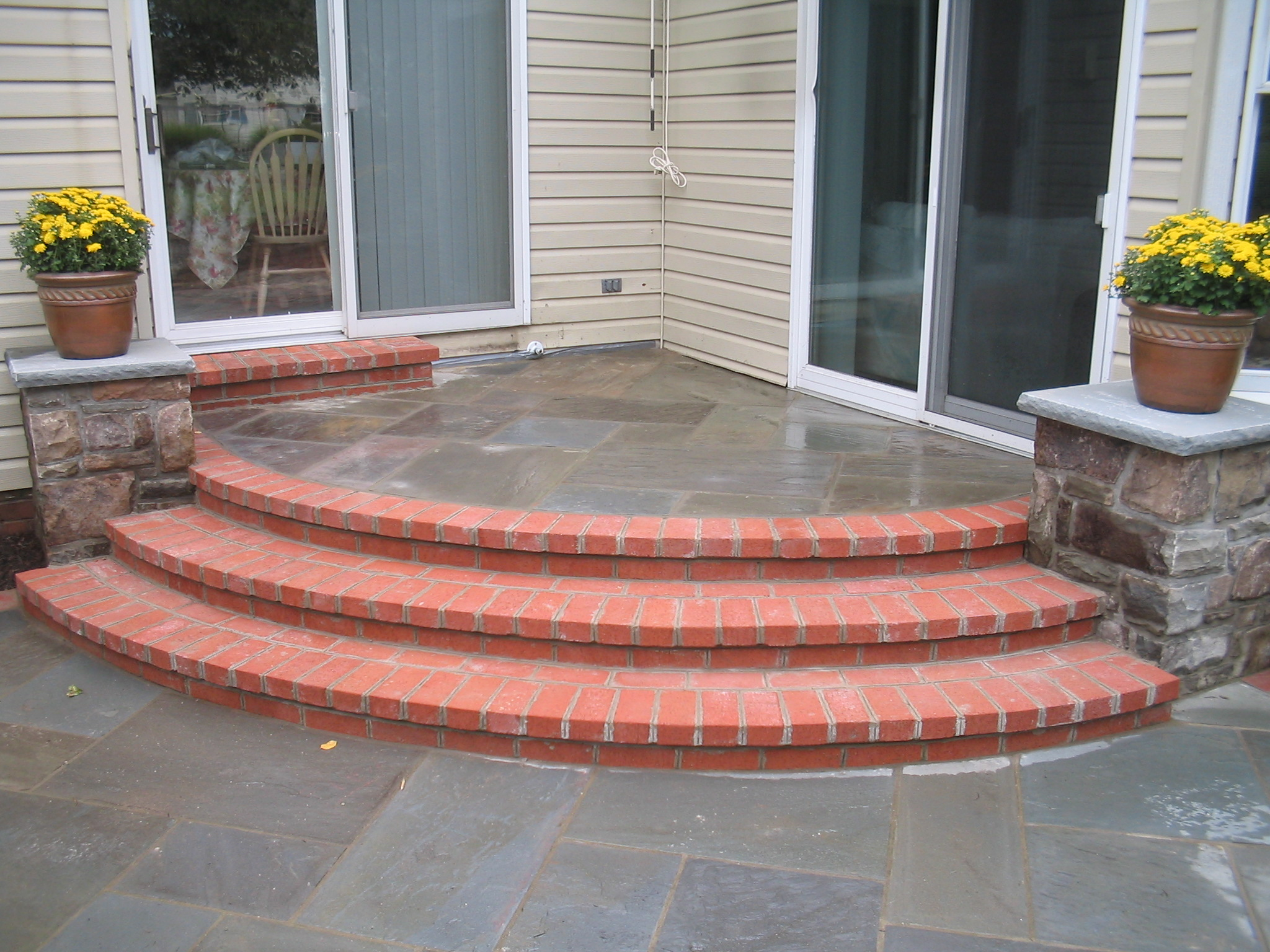 Corner Stone landing leading to brick steps and stone columns