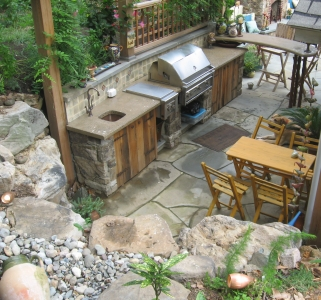 Outdoor kitchen featuring a concrete countertop, custom cabinets, wash sink and built-in barbeque.