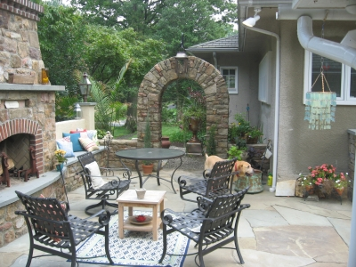 Stone archway, fireplace accented with brick and a stone & stucco seat bench