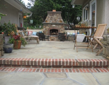 Brick & flagstone sitting area framed by a stone seat wall
