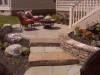 flagstone-patio-off-deck-with-boulders-stone-retaining-wall-and-stone-steppers-