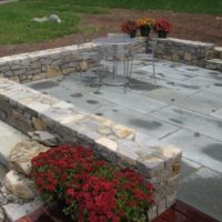 61 Stone Retaining and Sitting Walls Surround a Flagstone Patio