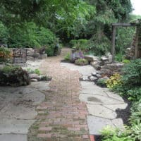 Narrow Yard Features Brick Walkway and Stone Relic Wall
