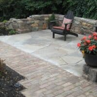 Flagstone Patio with Relic Stone Wall and Brick Walkway